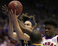 West Virginia forward Nathan Adrian (11) rebounds against Kansas guard Lagerald Vick, right, during the first half of an NCAA college basketball game in Lawrence, Kan., Monday, Feb. 13, 2017. (AP Photo/Orlin Wagner)