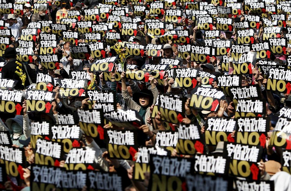 Protesters holding placards shout slogans at a rally against Japan's Prime Minister Abe's administration in the central Tokyo