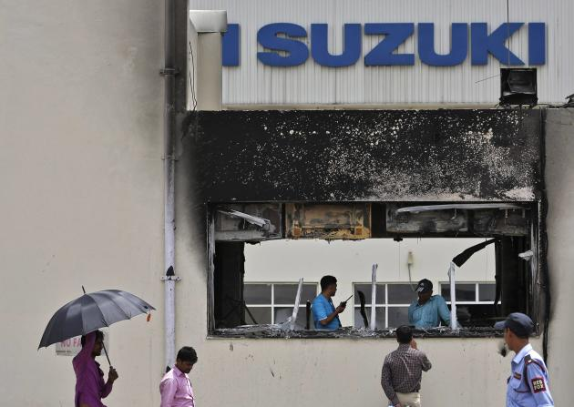 A media personnel speaks with employees behind a damaged portion of Maruti Suzuki's plant in Manesar