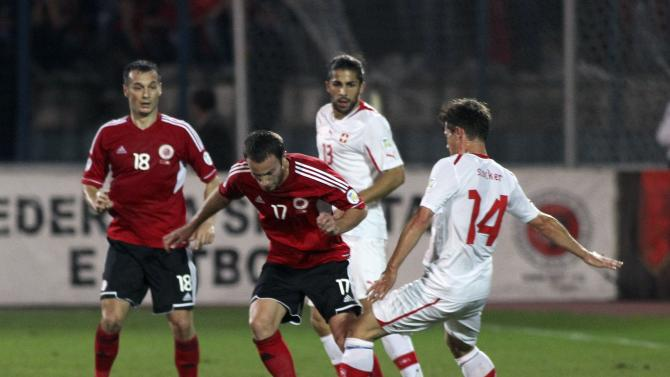 Switzerland's Valentin Stocker fights for the ball with Albania's Shkelzen Gashi during their 2014 World Cup qualifying soccer match in Tirana