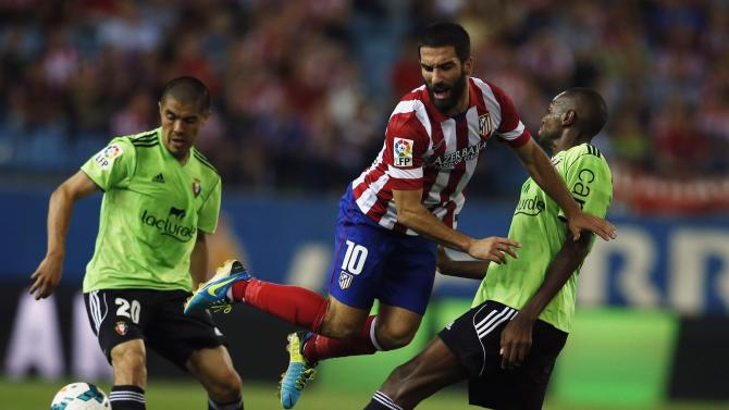 Atletico Madrid's Turan jumps between Osauna's Loe and Silva during Spanish first division soccer match at Vicente Calderon stadium in Madrid