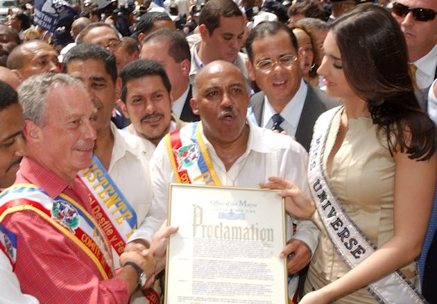 FILE - In this Aug. 10, 2003 file photo, New York City Mayor Michael Bloomberg, left, is honored by the President of the Dominican National Parade Nelson Pena, center, and Miss Universe, Amelia Vega,