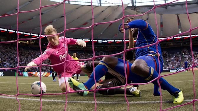 Vancouver Whitecaps' goalkeeper David Ousted, left, of Denmark, dives and makes the save on Colorado Rapids' Edson Buddle, right, as Whitecaps' Brad Rusin, back, defends during the first half of an MLS soccer game in Vancouver, British Columbia, on Sunday, Oct. 27, 2013