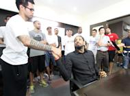 Renaldo Balkman shakes hands with Ronald tubid while the rest of the Petron Blaze Boosters look on at the PBA head office. (PBA Images)