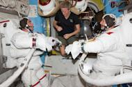 "Flight Engineers Chris Cassidy (left) and Luca Parmitano participate in a ""dry run"" in the International Space Station's Quest airlock in preparation for the first of two spacewalks in July 2013. Flight Engineer Karen Nyberg (center) assists."