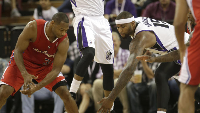 Sacramento Kings center DeMarcus Cousins, right, chases after the ball against Los Angeles Clippers guard Willie Green, left, during the third quarter of an NBA preseason basketball game in Sacramento, Calif., Monday, Oct. 14, 2013.   The Kings won 99-88