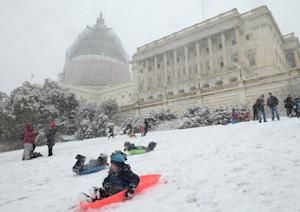 Children ride sleds down a hill on the West Lawn of …
