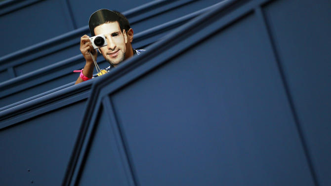 A fan, wearing a mask of tennis player Serbia's Novak Djokovic, takes pictures during the singles tennis match between Djokovic and Spain's Feliciano Lopez at the Shanghai Masters tournament