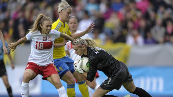 Poland's goalie Katarzyna Kiedrzynek, right, grabs the ball in front of Sweden's Nilla Fischer, middle, with the help of Poland's Nicole Krzysik, left, during the ladies' football World Championships qualification match at Swedbank Stadium in Malmo, Sweden, Saturday Sept. 21, 2013. (AP photo / Scanpix Sweden, Bjorn Lindgren)