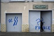 A worshiper opens the door of a mosque where nazi graffiti had been sprayed, on December 20, 2011 in Décines, a neighboring suburb of the French southeastern city of Lyon. Vandals have targeted a French mosque in Ozoir-La-Ferriere, a small town 35 kilometres (20 miles) east of Paris, in a graffiti attack, tagging the worship centre with swastikas and anti-Islam slogans, officials said Sunday
