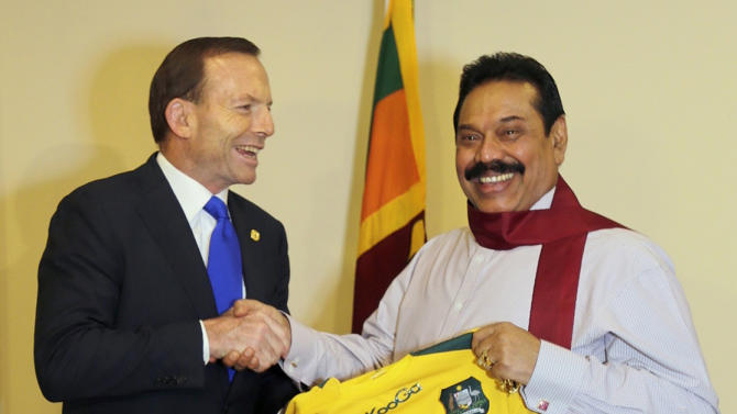 Australia's PM Abbott, who is currently in Sri Lanka to attend the CHOGM 2013, shakes hands with Sri Lanka's President Rajapaksa in Colombo