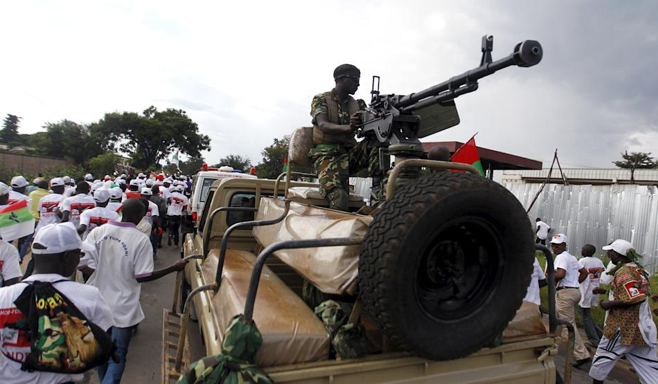 A Burundi military officer holds his machine gun as supporters of the CNDD-FDD party leave after their congress in the capital Bujumbura