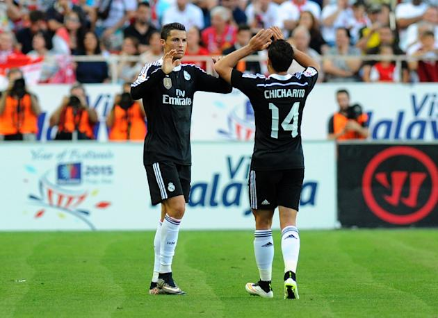 Real Madrid's Cristiano Ronaldo (L) celebrates with teammate Chicharito after scoring during the Spanish league football match against Sevilla in Sevilla on May 2, 2015