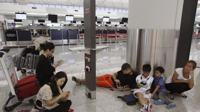 South Korea, Philippines and Poland passengers whose flights are cancelled in anticipation to typhoon Usagi, charge their mobile devices at Hong Kong International Airport