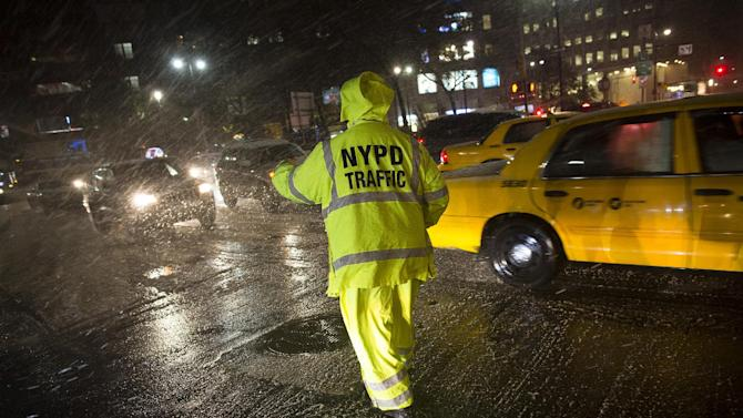 A NYPD traffic officer works in the financial district as sleet and snow blows around him, Wednesday, Nov. 7, 2012, in New York. Residents of New York and New Jersey who were flooded out by Superstorm Sandy are waiting with dread Wednesday for the second time in two weeks as another, weaker storm heads toward them and threatens to inundate their homes again or simply leave them shivering in the dark for even longer. (AP Photo/John Minchillo)