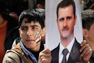 A Syrian demonstrator holds a portrait of President Bashar Al-Assad during a pro-regime rally in Damascus