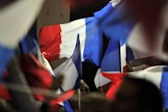 Supporters wave French flags during a campaign meeting of incumbent President Nicolas Sarkozy in the southwestern city of Avignon