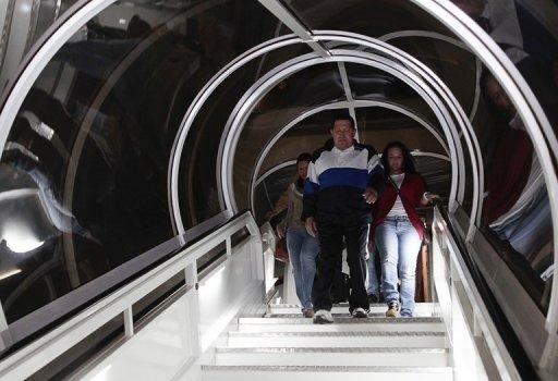 This photo provided by the Venezuelan presidency shows Venezuala's President Hugo Chavez walking down stairs with his daughter after returning from Cuba 7 December 2012. Cuba was on edge as Chavez underwent more cancer surgery, with many here worried that if he dies, deeply dependent Cuba will plunge into economic disarray.