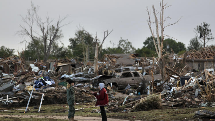 A member of a security team, left, talks with a local resident who was allowed by security officers into a virtually sealed off neighborhood, amid the rubble of destroyed homes, one day after a tornado moved through Moore, Okla., Tuesday, May 21, 2013. The huge tornado roared through the Oklahoma City suburb Monday, flattening entire neighborhoods and destroying an elementary school with a direct blow as children and teachers huddled against winds. (AP Photo/Brennan Linsley)