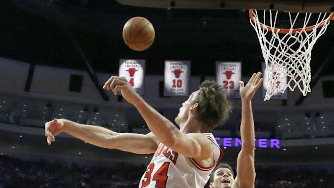 Chicago Bulls forward Mike Dunleavy (34) blocks the shot of Boston Celtics forward Kris Humphries (43) during the second half of an NBA basketball game on Thursday, Jan. 2, 2014, in Chicago. The Bulls won 94-82