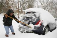 Oretha Bailey clears her car of snow in Silver Spring, Maryland February 13, 2014. REUTERS/Gary Cameron