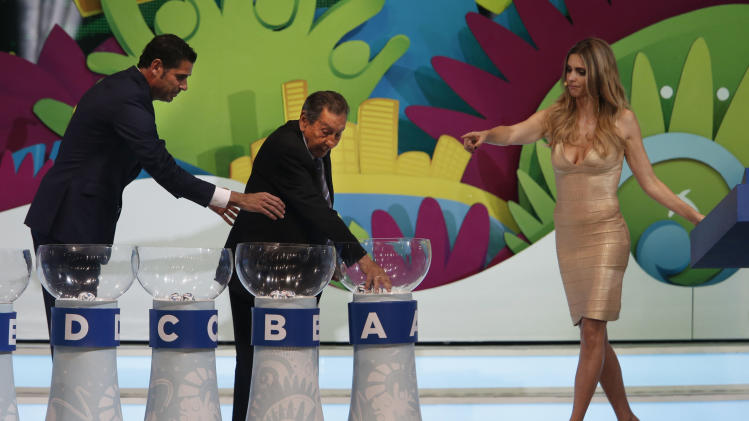 Former soccer great and World Cup winner Alcides Ghiggia of Uruguay is supported by former World Cup player Fernando Hierro of Spain, left, and Brazilian actress Fernanda Lima, right, during the draw ceremony for the 2014 soccer World Cup in Costa do Sauipe near Salvador, Brazil, Friday, Dec. 6, 2013