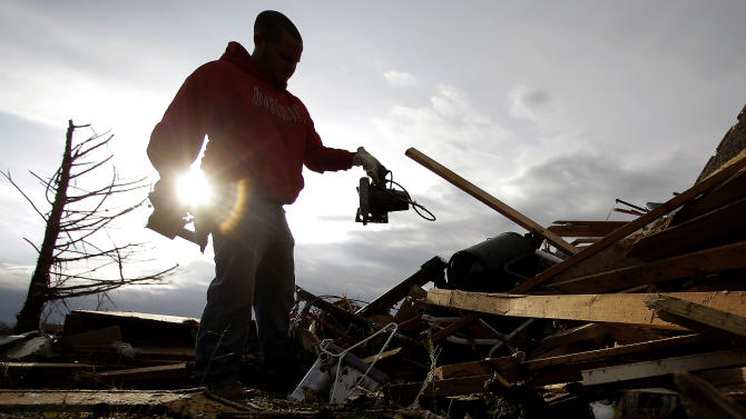 Zac Woodcock salvages items from the rubble of a tornado-ravaged rental home which they own Tuesday, May 21, 2013, in Moore, Okla. A huge tornado roared through the Oklahoma City suburb Monday, flattening an entire neighborhoods and destroying an elementary school with a direct blow as children and teachers huddled against winds. (AP Photo/Charlie Riedel)
