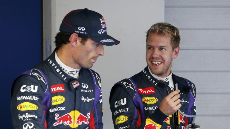 Red Bull Formula One driver Vettel smiles at teammate Webber after the qualifying session for the Korean F1 Grand Prix in Yeongam