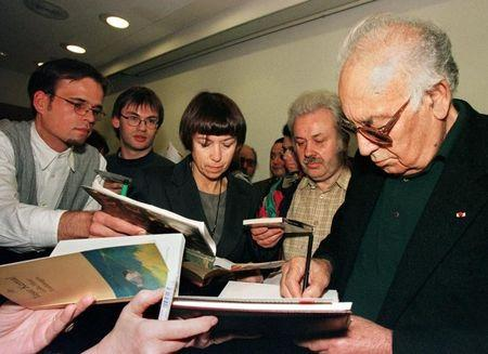 Turkish writer Yasar Kemal (R) gives autographs after a press conference at the 49th  Germany bookfair