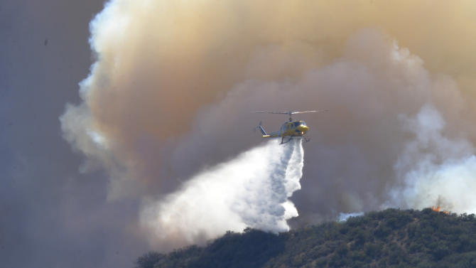 Residents watch a a helicopter drop water during a wildfire that burned several thousand acres, Thursday, May 2, 2013, in Ventura County, Calif.   (AP Photo/Mark J. Terrill)