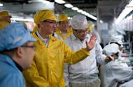 """A picture from Apple of chief executive Tim Cook (in yellow) visiting the iPhone production line at the Foxconn factory in Zhengzhou in China's Henan province in March. Cook has vowed that creativity will remain in the company's """"DNA"""" and hinted that products on the horizon may come in the area of television"""