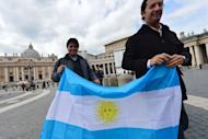 """People hold an Argentinian flag on St Peter's square on March 15, 2013 at the Vatican. Pope Francis on Friday urged the troubled Catholic Church not to give in to """"pessimism"""" and to find new ways of spreading the faith """"to the ends of the earth"""""""