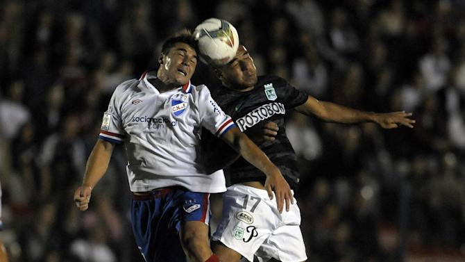 Rafael Garcia of Uruguay's Nacional, left, fights for the ball with Jefferson Duque of Colombia's Atletico Nacional during a Copa Libertadores soccer game in Montevideo, Uruguay, Tuesday, March 18, 2014