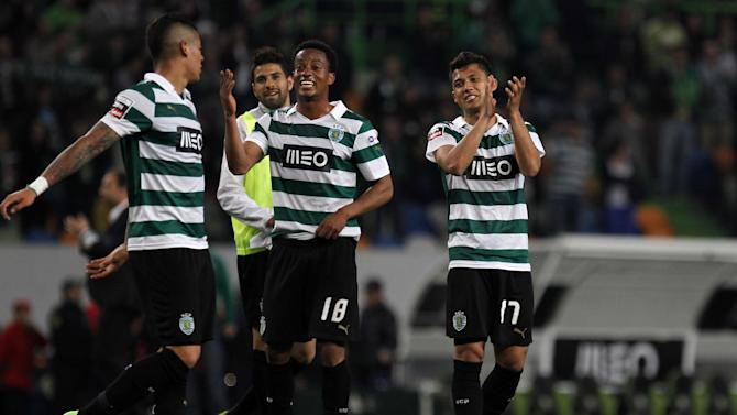 Sporting's Freddy Montero, right, from Colombia, Andre Carrillo, center, from Peru, and Marcos Rojo, from Argentina, celebrate at the end of the Portuguese league soccer match between Sporting and Porto at Sporting's Alvalade stadium, in Lisbon, Sunday, March 16, 2014. Sporting won 1-0