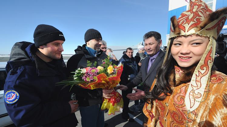Russian cosmonauts Oleg Novitsky, left, and Yevgeny Tarelkin, second left, are greeted with flowers upon arrival at an airport in Kostanai, Kazakhstan, Saturday, March 16, 2013, after they return to the earth with NASA's astronaut Kevin Ford, not in the photo, in a Soyuz space capsule. The Soyuz space capsule carrying the three men landed Saturday morning on the steppes of Kazakhstan after 144 days aboard the International Space Station, ISS. (AP Photo/Alexander Nemenov, Pool)