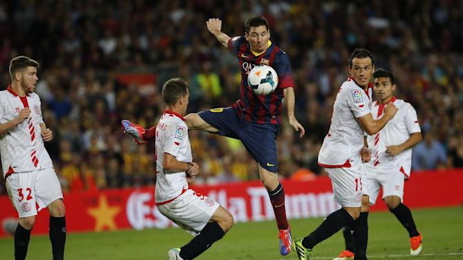 FC Barcelona's Lionel Messi from Argentina, center, in action with Sevilla's Fernando Navarro, left, and Piotr Trochowski from Poland, right, during a Spanish La Liga soccer match at the Camp Nou stadium in Barcelona, Spain, Saturday, Sept. 14, 2013