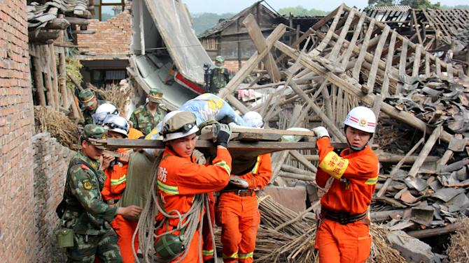In this photo released by China's Xinhua News Agency, rescuers carry out an elderly paralyzed person from a collapsed house after an earthquake struck, in Qingren Township, Lushan County, Ya'an City, southwest China's Sichuan Province, Saturday, April 20, 2013. A powerful earthquake struck the steep hills of China's southwestern Sichuan province Saturday morning, leaving at least 160 people dead and more than 6,700 injured. (AP Photo/Xinhua, Le Xiaoxuan) NO SALES