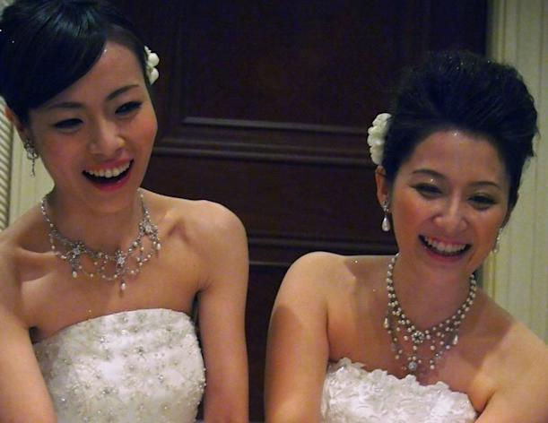 Lesbian couple Koyuki Higashi (L) and Hiroko light a candle at their wedding reception in Tokyo on March 1, 2013. They became the first gay couple to tie the knot at Tokyo Disney Resort, both decked out in fairytale white dresses despite an initial ruling that one had to wear men's clothes