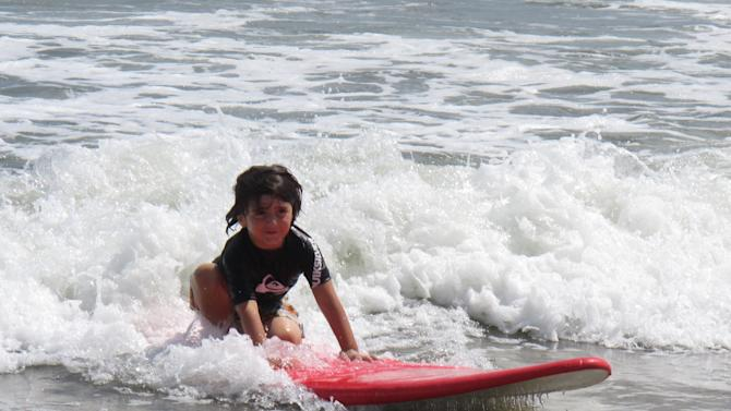 In this Aug. 28, 2012 photo, 5-year-old Dane Michael Valenti of Hasbrouck Heights N.J. rides a wave into shore on a surfboard in Belmar, N.J. New Jersey's Top Ten beaches contest is suspending voting this summer on the best beach in the state, focusing instead on cooperation among regional tourism leaders to promote the shore as a whole as it recovers from Superstorm Sandy. (AP Photo/Wayne Parry)