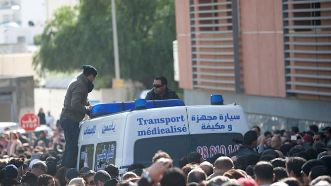 People throng the streets as an ambulance carries the body of Tunisian opposition leader Chokri Belaid outside the hospital towards the morgue, after he was shot to death in Tunis, Wednesday, Feb. 6, 2013.  A critic of the Islamist-led government and violence by radical Muslims, Belaid was killed outside his home Wednesday, in the first political assassination in post-revolutionary Tunisia. The killing is likely to heighten tensions in the North African nation whose path from dictatorship to democracy so far has been seen as a model for the Arab world. (AP Photo/Amine Landoulsi)