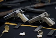 "Weapons and jewellery seized from Jorge Eduardo Costilla Sanchez, aka ""El Coss"", are presented to the press in Mexico City. The capture of the Gulf cartel's kingpin may have crippled the once mighty gang, but its downfall could usher in more violence in Mexico as powerful rivals battle for supremacy, analysts said"