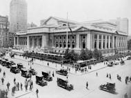 Pedestrian and automobile traffic crosses in front of the New York Public Library on July 14, 1915.
