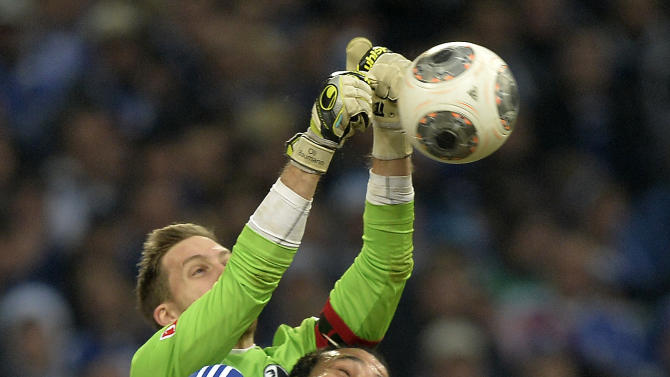 Freiburg goalkeeper Oliver Baumann saves a ball  next to  Schalke's Joel Matip during the German Bundesliga soccer match between FC Schalke 04 and SC Freiburg in Gelsenkirchen, Germany, Sunday, Dec. 15, 2013