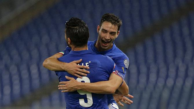 Italy's Pelle celebrates with his teammate De Sciglio after scoring against Norway during their Euro 2016 group H qualifying soccer match at the Olympic Stadium in Rome