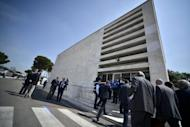 People are seen walking towards the building where a trial organized by the Italian football federation (FIGC) takes place, on May 31, in Rome. 54 football players and 22 clubs will be scrutinised until June 4 or 5, in matchfixing cases