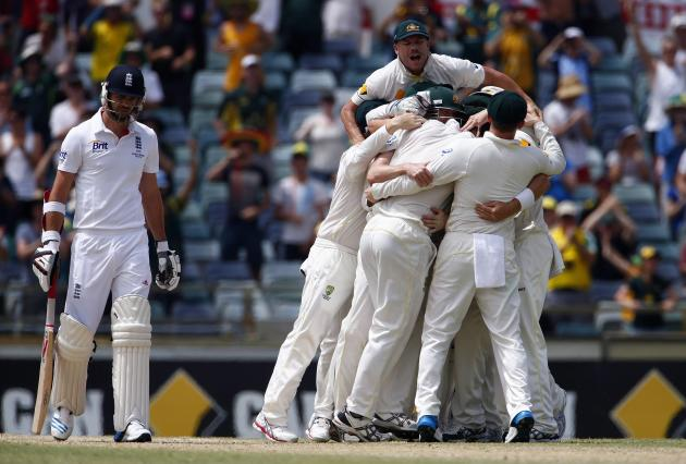 Australia's players celebrate winning the Ashes test cricket series against England as England's James Anderson reacts at the WACA ground in Perth
