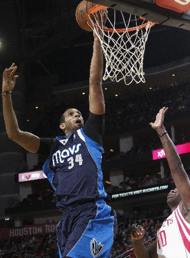 Dallas Mavericks forward Brandan Wright (34) drives for a layup past Houston Rockets forward Ronnie Brewer (10) during the first half of an NBA basketball game, Monday, Dec. 23, 2013, in Houston