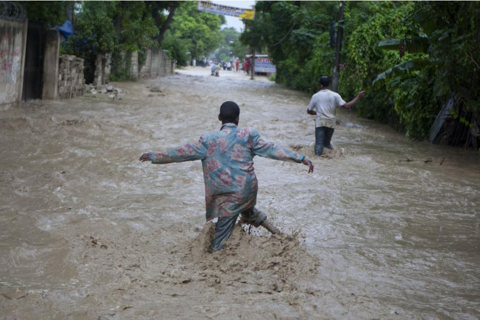 Residents wade through a flooded street caused by heavy rains from Hurricane Sandy in Port-au-Prince, Haiti, Thursday, Oct. 25, 2012. Hurricane Sandy rumbled across mountainous eastern Cuba and headed