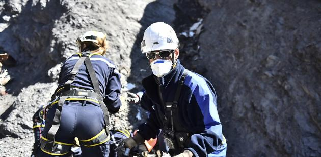 In this photo taken on Tuesday, March 31, 2015 and provided by the French Interior Ministry, French emergency rescue services work among debris of the Germanwings passenger jet at the crash site near Seyne-les-Alpes, France. The heads of Lufthansa and its low-cost airline Germanwings are visiting the site of the crash that killed 150 people amid mounting questions about the co-pilot and how much his employers knew about his mental health. (AP Photo/Yves Malenfer, Ministere de l'Interieur)
