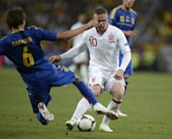 English forward Wayne Rooney (R) is challenged by Ukrainian midfielder Denys Garmash during their Euro 2012 match on June 19. England rode their luck to top Euro 2012 Group D as they beat co-hosts Ukraine 1-0